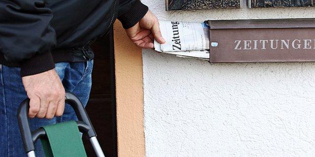 Nahaufnahme einer Hand, die eine Zeitung in einen Zeitungsbriefkasten steckt