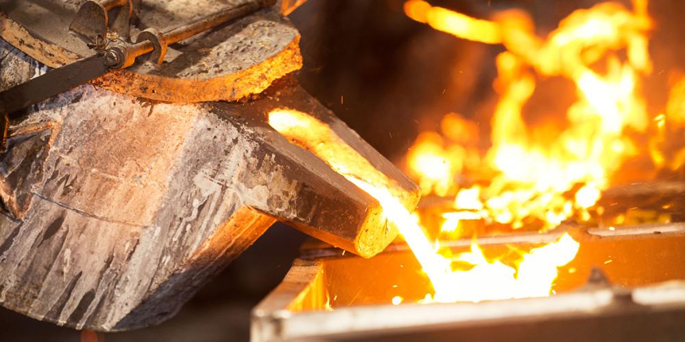 Gusseisenbehälten mit flüssigem Stahl wird in eine Gussform gekippt