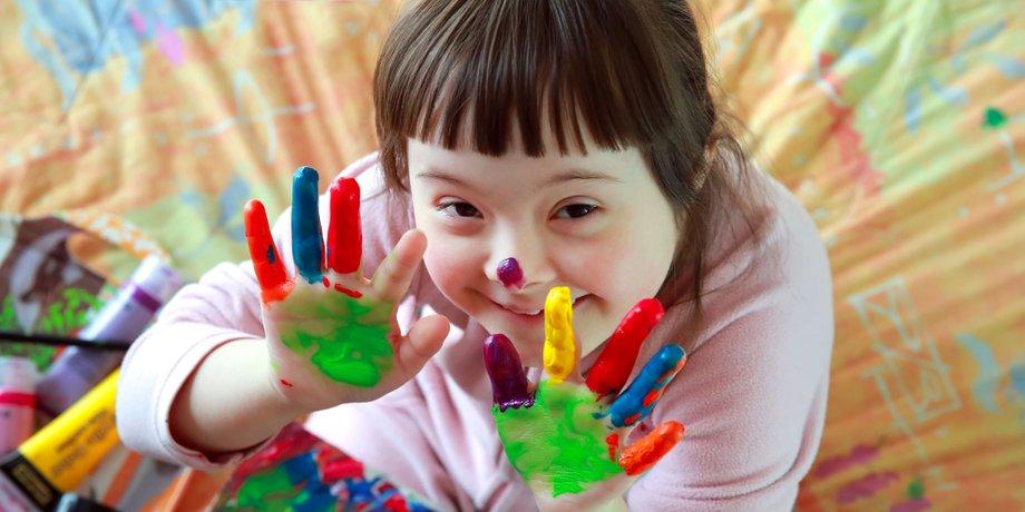 Kind mit Down-Syndrom und bemalten Händen