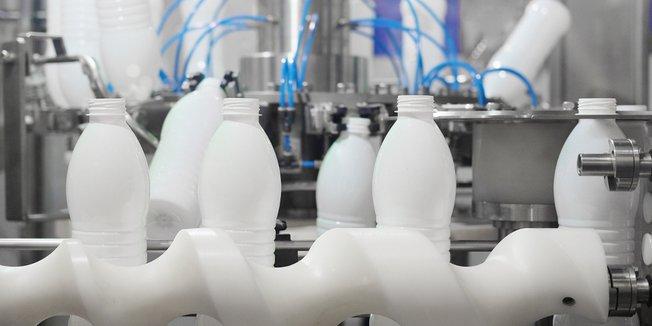 Industrielle Maschine mit weißen Plastikflaschen auf Fließband