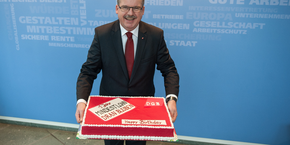 """DGB-Vorstandsmitglied Stefan Körzell mit """"Mindestlohn-Geburtstagstorte"""""""