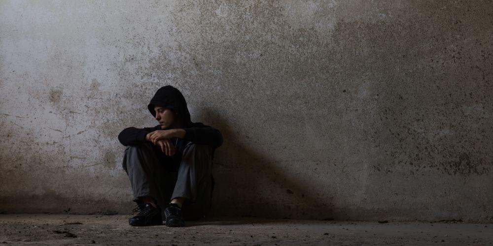 Deprimierter Jugendlicher vor einer Mauer