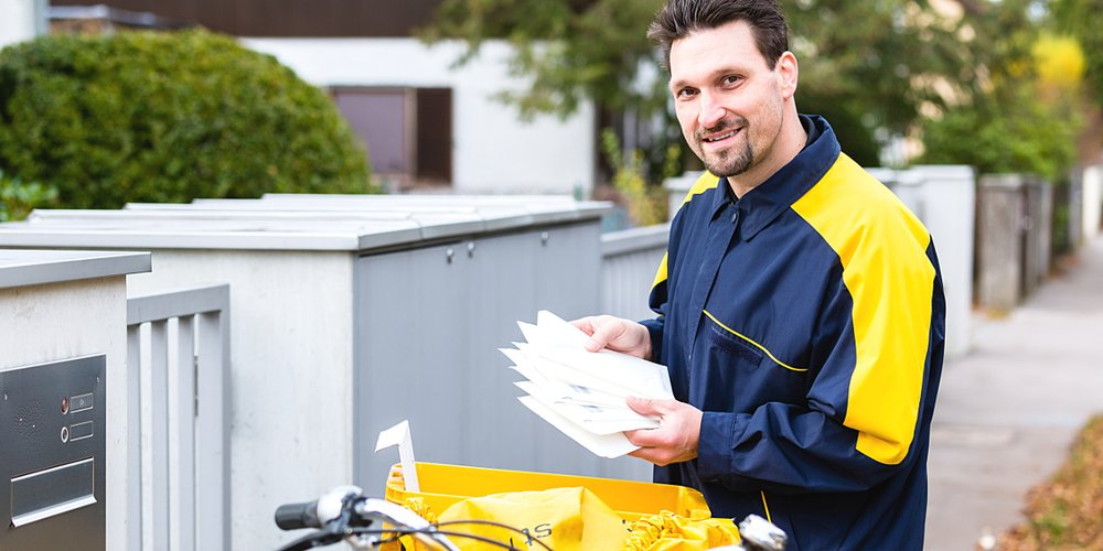 Briefträger wirft Briefe in Briefkasten