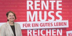 """DGB-Vorstand Annelie Buntenbach vor einem Plakat der DGB-Rentenkampagne mit der Aufschrift """"Rente muss für ein gutes Leben reichen"""""""
