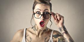 tätowierte und gepiercte junge Frau mit Brille schaut überrascht