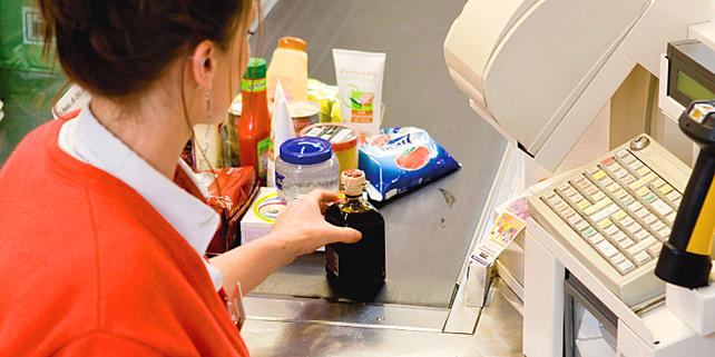 Kassiererin zieht Waren über Scanner, Kasse, Supermarkt