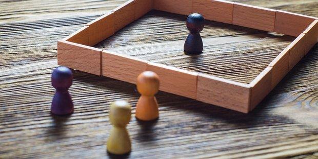 vier Spielfiguren aus Holz, eine davon steht ausgegrenzt hinter einer Mauer