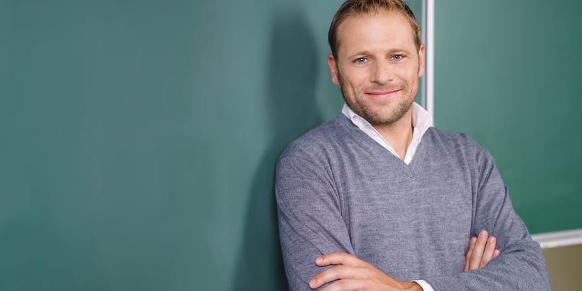 Lächelnder Mann vor Schultafel