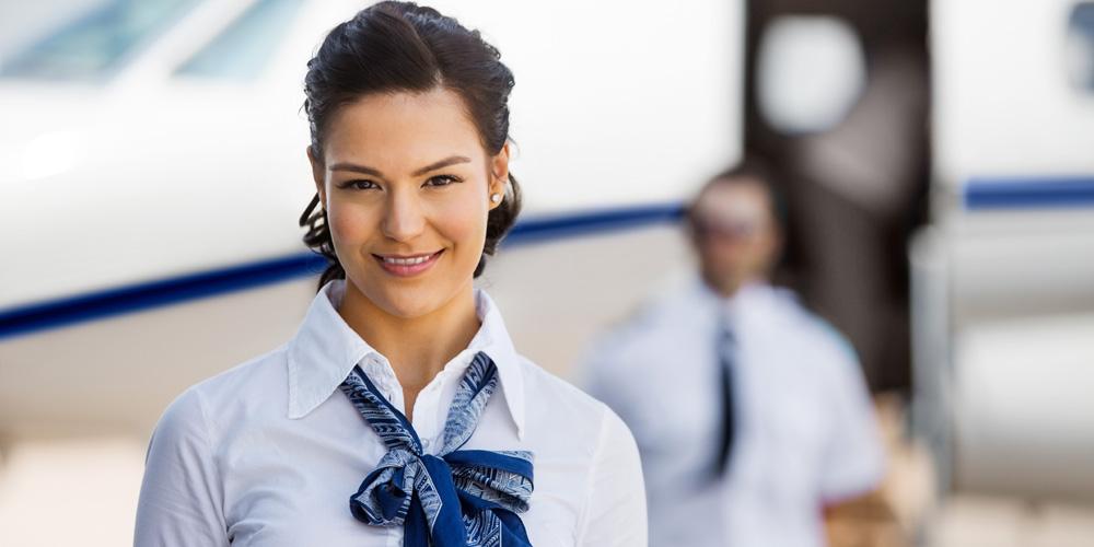lächelnde Flugbegleiterin steht vor Flugzeug
