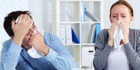 Ein Mann und eine Frau (Büroumgebung / Schreibtisch) benutzen Taschentücher und halten sich den schmerzenden Kopf