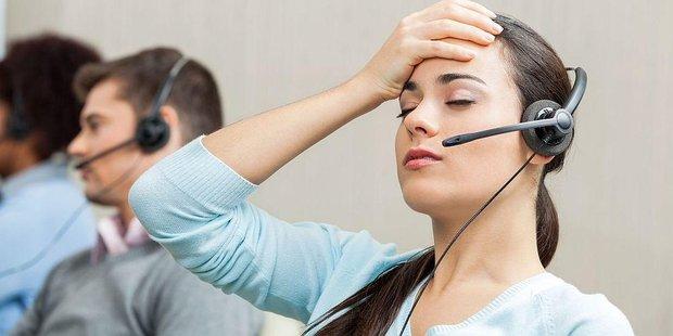 Frau im Callcenter fässt sich mit Hand an die Stirn und schliesst die Augen