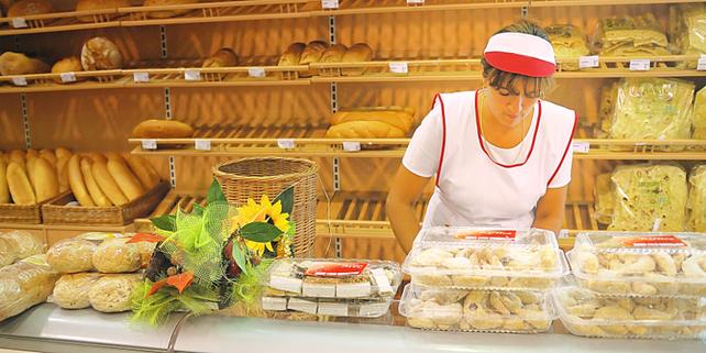 Bäckereifachverkäuferin hinter Theke von Bäckerei