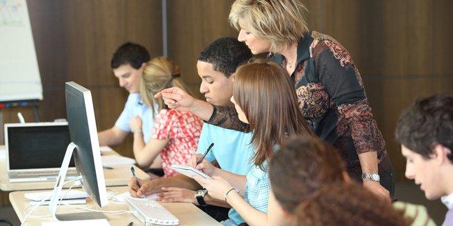 Lehrerin erklärt Schülern etwas an einen PC Bildschirm