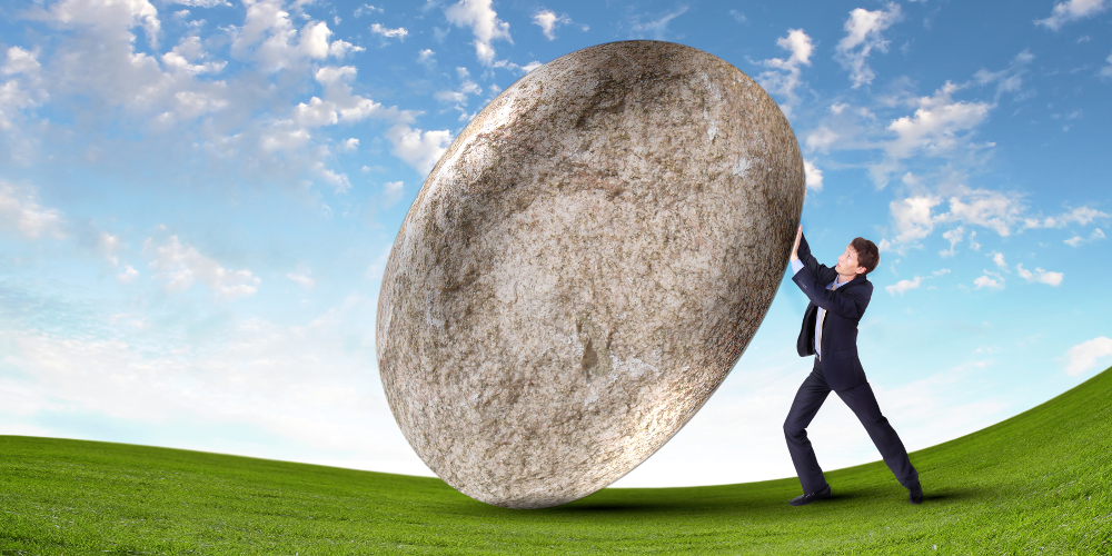 Mann versucht riesigen Stein zu bewegen
