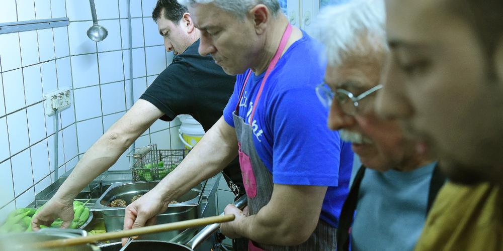 Vier Männer kochen in einer kleinen Küche