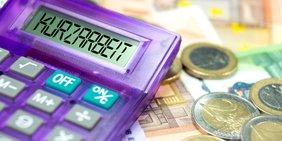 violetter Taschenrechner mit dem Schriftzug Kurzarbeitergeld im Display, rechts daneben liegen Geldscheine und Münzen