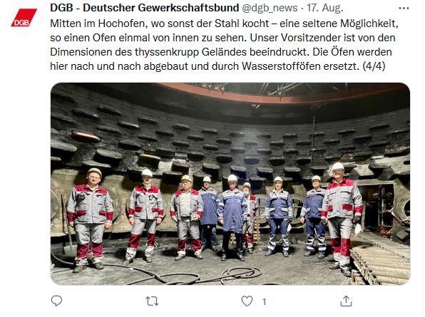Foto von Reiner Hoffmanns Sommerreise 2021 in Duisburg. Reiner Hoffmann mit Beschäftigten in Arbeitskleidung im inneren eines inaktiven Hochofens.