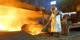 Stahlkocher mit Hitzeschutzmantel und Werkzeug am Feuerofen