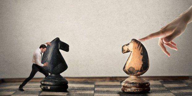 kleiner Mann und große Hand bewegen Schachfiguren