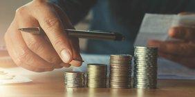 Männlcihe Hand mit mehreren Stapeln Münzen