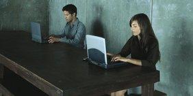Symbolbild Digitalisierung Crowdworking Arbeit 4.0; Mann und Frau vor Laptops an großem Tisch