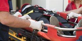 Rettungsbahre mit Person im Anzug darauf; im Vordergrund: Hand und Uniform eines Rettungssanitäters