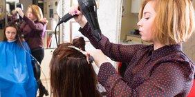 Junge Friseurin fönt Haare junger Kundin vor Spiegel
