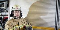 Feuerwehrmann mit Helm vor Feuerwehrauto; im Hintergrund ein aufgerollter Schlauch
