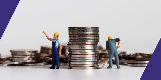 Zwei Miniaturfiguren Bauarbeiter und mehrere Stapel Münzen