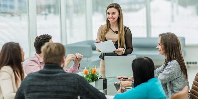 Männer und Frauen stehend an Konferenztisch bei Besprechung