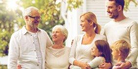 Großeltern, Eltern und Kinder posieren fröhlich vor einem Haus