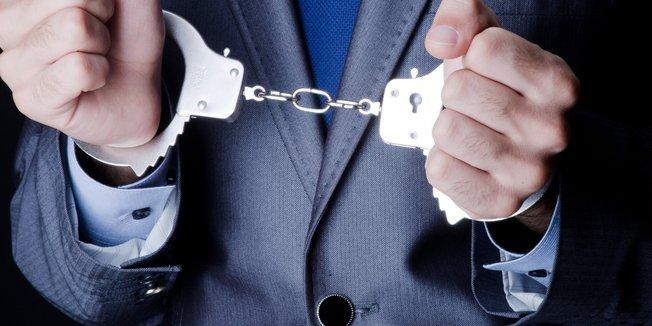 Nahaufnahme der Hände eines Mannes in Handschellen; Mann trägt Anzug und Krawatte