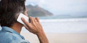 Nahaufnahme Mann am Strand mit Smartphone am Ohr
