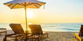 Zwei Liegen am Strand bei Sonnenuntergang