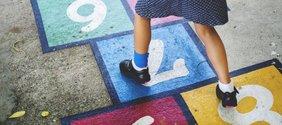 """Mädchen spielt auf der Straße """"Himmel und Erde"""""""