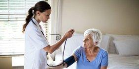 Pflegerin misst Blutdruck bei älterer Frau