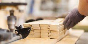 Hand an Einzelteilen Holz auf Maschine