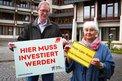 """Dieter Roß und Monique Menzel mit """"Hier muss investiert werden""""-Schild vor Kreishaus"""