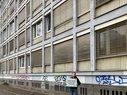 """Hans Jurdeczka vor Bürogebäude in Leipzig mit Schild """"Hier muss investiert werden"""""""