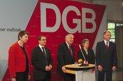 Gruppenbild des DGB-Bundesvorstandes. Die fünf Mitglieder stehend auf der Rednerbühne. Im Hintergrund das DGB-Logo.