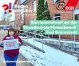 """Gudrun Baum vor Grundschule Maienbeeck in Bad Bramstedt mit """"Hier muss investiert werden""""-Schild."""