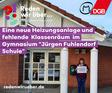 """Gudrun Baum vor Gymnasium Jürgen Fuhlendorf Schule in Bad Bramstedt mit """"Hier muss investiert werden""""-Schild."""