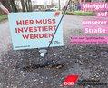 Schlagloch in Mönchengladbach und Minigolfschläger, Schild Hier muss investiert werden