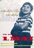 Motiv: Ein kleiner Junge lehnt lachend an einer Mauer.
