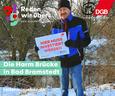 """Ralph Baum bei Harm Brücke in Bad Bramstedt mit """"Hier muss investiert werden""""-Schild."""