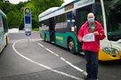 """Uwe Schuchmann mit """"Hier muss investiert werden""""-Schild vor Bus"""