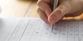 Nahaufnahme: Hand füllt Fragebogen aus